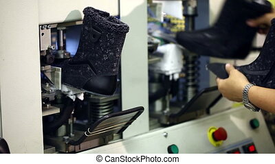 Working woman fixes blanks of boots with machine