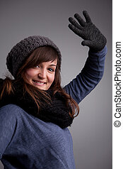 girl waving at camera with warm hat scarf and gloves