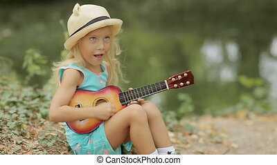 Cute little girl in straw hat playing on toy guitar in the...