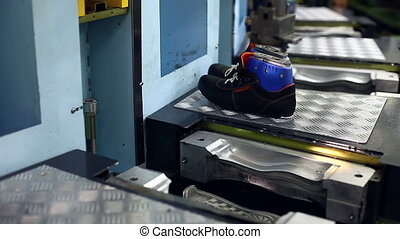 Working woman processing boots on machine