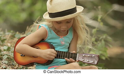 Beautiful little girl in straw hat playing on toy guitar