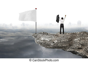 man cheering on cliff with white flag and cloudy cityscape -...