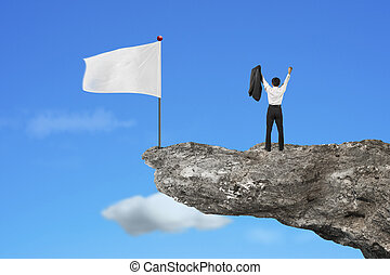 man cheering on cliff with blank white flag and sky