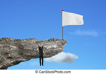 man hanging on cliff with blank white flag and sky
