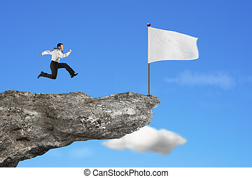 man running to blank white flag on cliff with sky