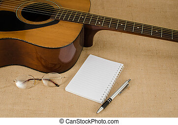 Part of acoustic guitar with blank paper on brown sack...
