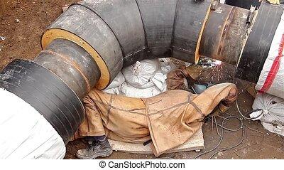 Welder is welding the pipeline - Metal worker welds two big...
