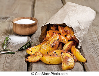 Baked potato wedges in paper bag on rustic table