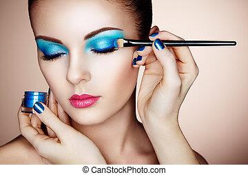Makeup artist applies eye shadow. Beautiful woman face....