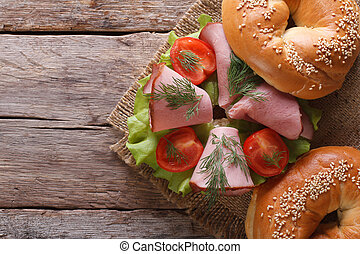 bagel with ham on an old wooden table top view horizontal -...