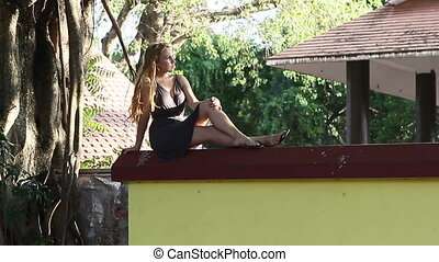 young beautiful blonde girl sitting on the fence posing near...