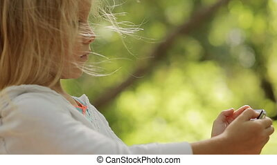 Close up of cute little girl making selfie in the forest