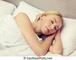beautiful woman sleeping in bed - hotel, travel and...