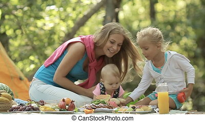 Young mother and little daughter playing with baby on a picnic