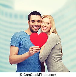smiling couple holding big red heart - couple, love and...