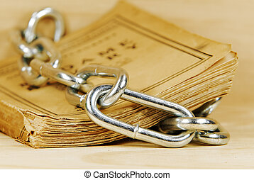 censorship - an old book surrounded by chain