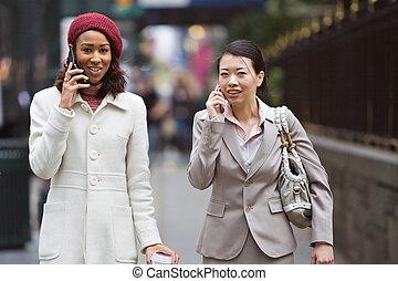 Business Women Walking - Two business women walking in the...
