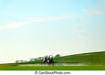 spraying pesticide - a tractor spraying pesticide in a...