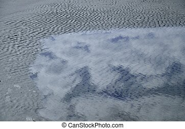 Cloud reflections in a tidal pool along the beach