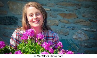 beautiful girl and geranium flowers - portrait of young...