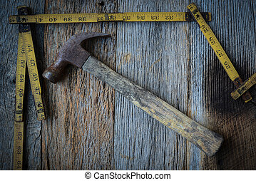 Old Tape Measure and Hammer for Construction on Rustic Wood...