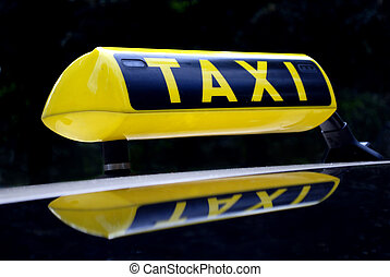 yellow neon taxi sign mirroring in the car roof
