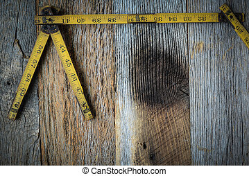 Old Tape Measure for Construction on Rustic Wood Background