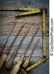 Rustic Screwdrivers and Tape Measure on Wood Background -...