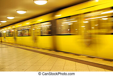 yellow passing berlin metro train with motion blur