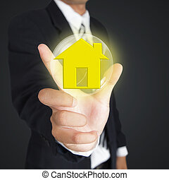 Hand holding bubble with home sign