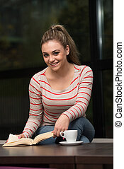 Smiling Young Student In Cafe Reading Book - Young Female...