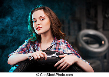 Beautiful auto mechanic Beautiful young woman holding work...