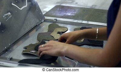 Worker puts stitched parts for production of boots, close-up