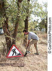 "man digging near the sign ""forbidden to dig"""