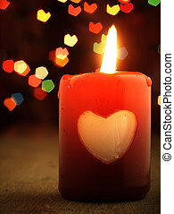 Red candle on the table and shiny hearts in background. -...