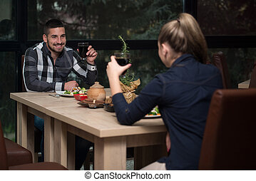 Couple Having Dinner In A Restaurant - Friends Eating At A...