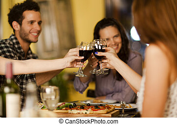 Group of friends toasting with wine at a restaurant