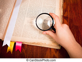 Hand with magnifier glass over old book