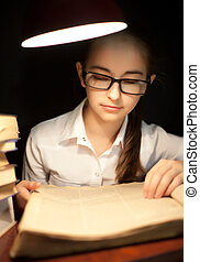 Young girl reading book under lamp