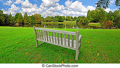 Parkbench By Pond - Parkbench by a small pond in a park on a...
