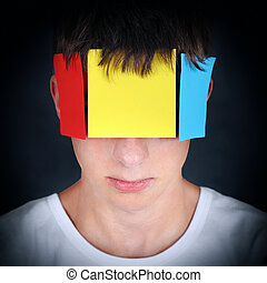 Colored Paper on the Face - Portrait of Teenager on the dark...