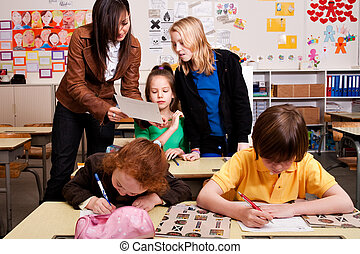 Teacher is correcting the piece of paper - Group of little...