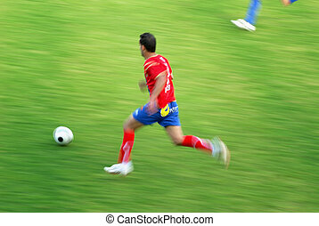 professional soccer player running after the ball in a...