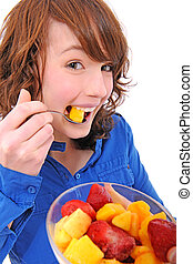 young woman eating fruit salad - happy young woman eating...
