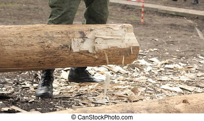 Soldier in camouflage with an ax sharpening log