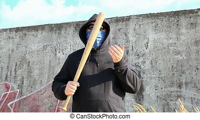 Man with a baseball bat at outdoor near wall