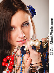 summer girl with plenty of jewellery, beads in hands -...