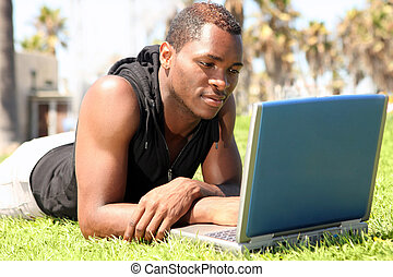 Student of African Amercian Descent Wotking on a Laptop