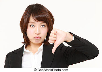 thumbs down - studio shot of young Japanese businesswoman