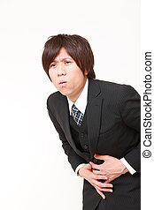 stomachache - studio shot of young Japanese businessman on...